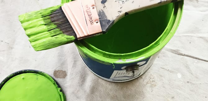 Green paint in a can on a cover with a paint brush.